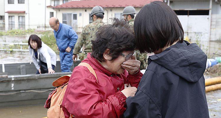 En äldre kvinna blir tröstad av en annan kvinna