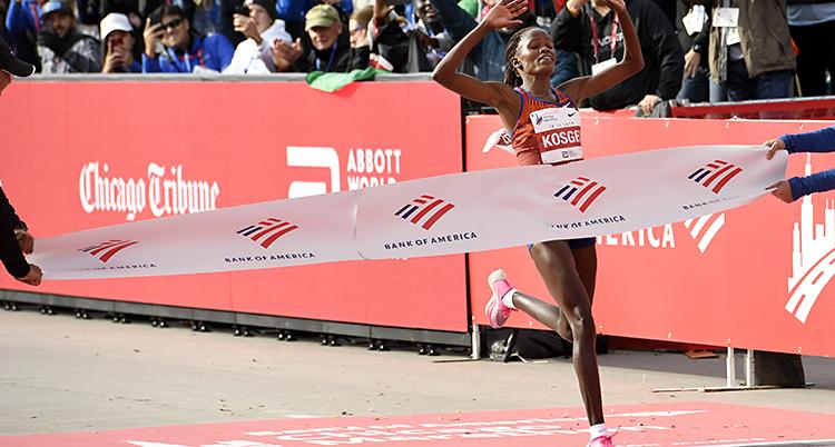 Brigid Kosgei springer ggenom ett tyg vid mållinjen