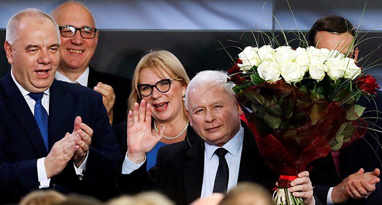 Partiet Lag och rättvisa vann stort i helgens val. Ledaren Jaroslaw Kaczynski vinkar med ena handen. I den andra har han en bukett vita rosor. Runt honom står flera andra glada politiker.