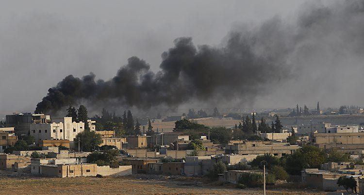 Svart rök kommer från bombade hus