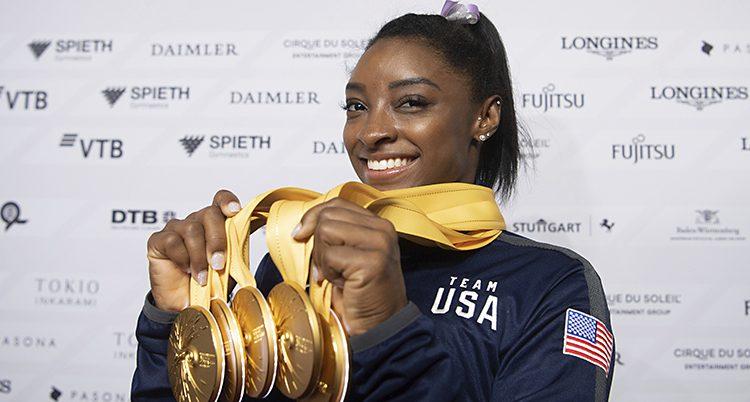 Simone ler och håller upp fem tunga medaljer.