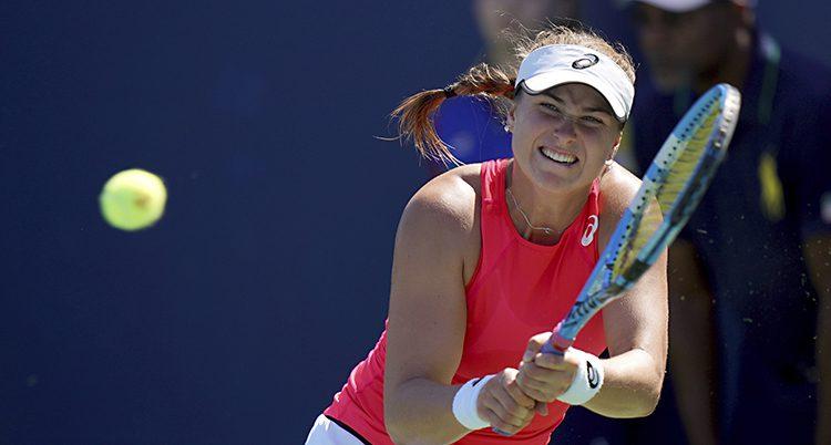 Rebecca tar i och slår ett hårt slag. Bollen är i luften och är på väg från hennes racket.