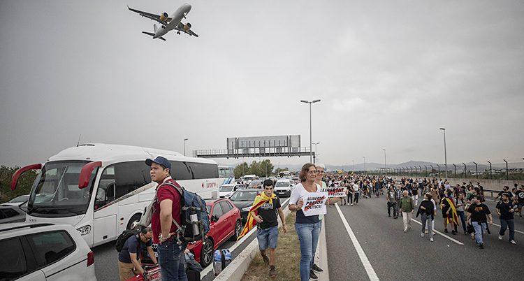 Bilden är tagen nära Barcelonas flygplats. En massa folk går på ena sidan av vägen. Den är blockerad. Inga bilar kan köra där. På andra sidan vägen kör bilar. Ovanför i luften syns ett flygplan.