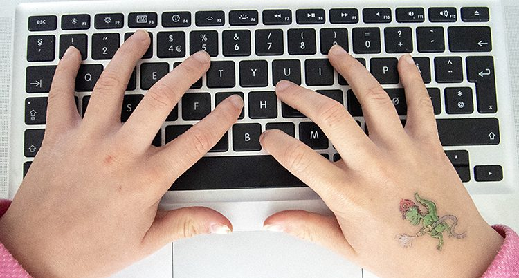 Ett barns händer ligger på ett tangentbord.
