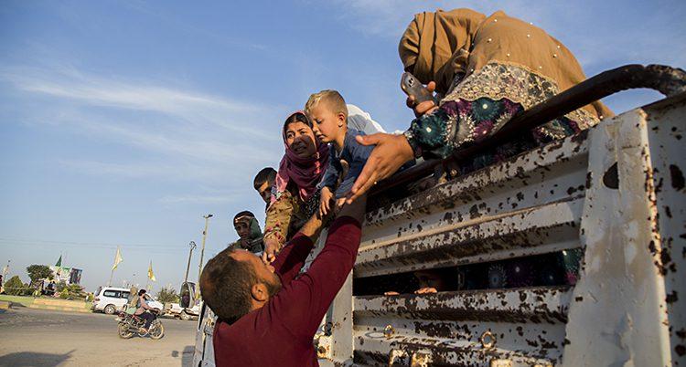 En man lyfter upp ett barn till en lastbil.