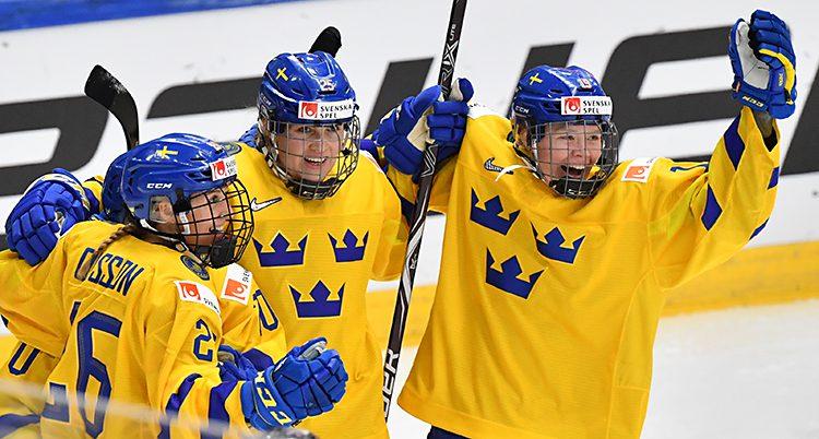 Bilden är från ishockey-VM för damer. Sverige har precis gjort mål. Tre spelare jublar. De har gula tröjor med tre blå kronor på, och blå hjälmar.