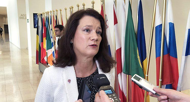 Ann Linde blir intervjuad. Hon har mikrofoner framför sig. I bakgrunden syns flera flaggor från olika EU-länder.