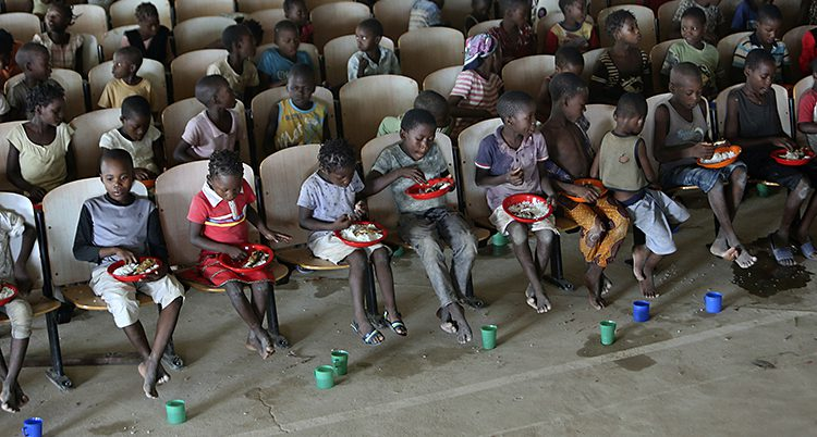 Barn på rad sitter och äter i ett tält. Framför sig har de gröna muggar med vatten.