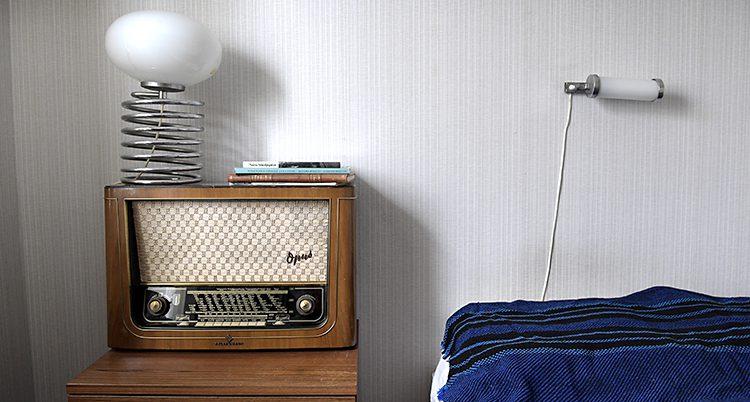 En bild på en gammal radioapparat. Den står bredvid en säng som har ett blått sängöverkast. På radion står en lampa.