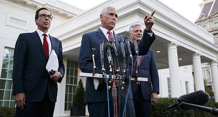 Mike Pence i kostym ser allvarlig ut och pekar med handen i luften. Han står framför flera mikrofoner. Bakom honom två allvarliga män.
