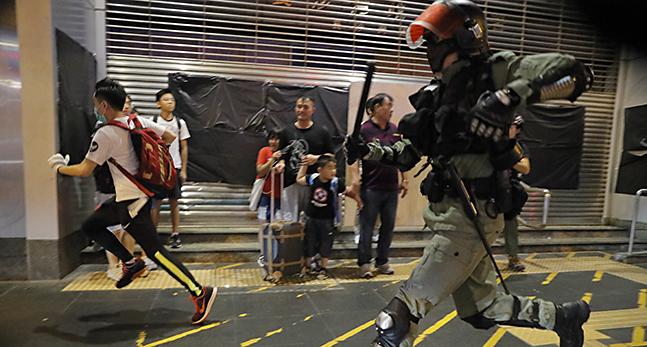 Folk tittar på när en polis jagar en demonstrant. Polisen har en batong och kraftiga skyddskläder. Bland annat en hjälm med visir.