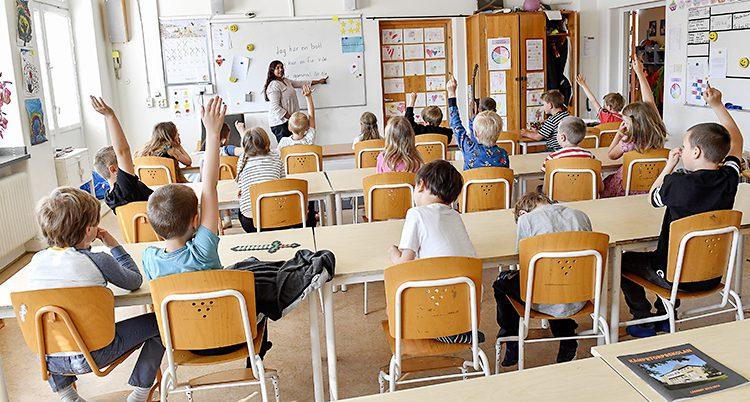 Elever sitter i ett klassrum och tittar mot läraren. Några räcker upp handen