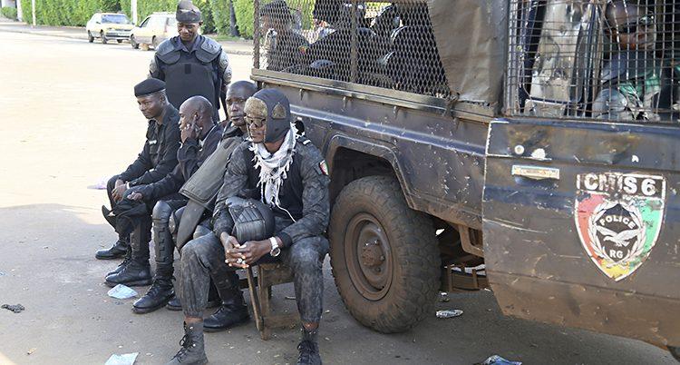 Poliser sitter med vapen bredvid en smutsig bil