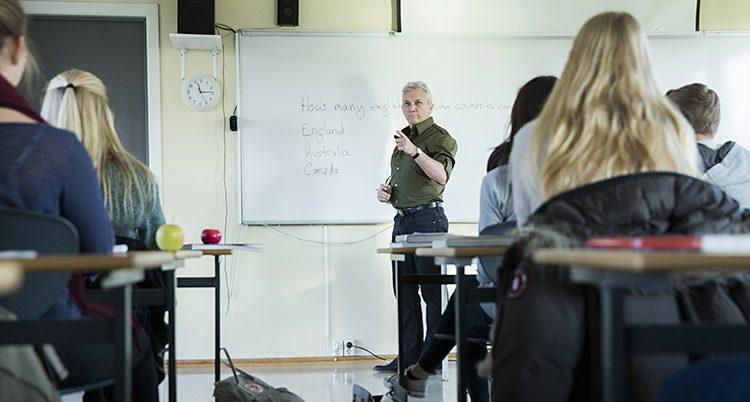 En lärare står vid en tavla i ett klassrum. Några skolbänkar syns.