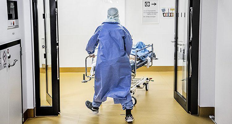 En person i operationskläder drar en sjukhussäng.