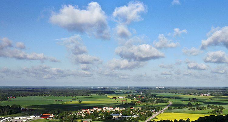Ett vackert landskap med åkrar blå himmel och vita moln.
