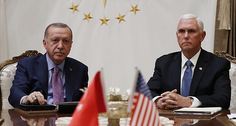 Två män sitter vid ett bord. De har kostym. Närmast i bilden syns två små flaggor. En turkisk flagga och en amerikansk flagga.