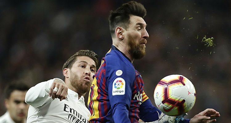 Närbild på två spelare. Bollen är i luften framför Messis bröst .Ramos fgörsöker att nå den med foten.