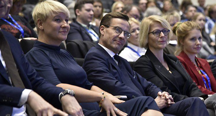 Kristersson sitter bland många andra politiker i publiken