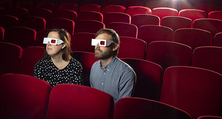 De sitter i en biosalong med 3D-glasögon på sig.