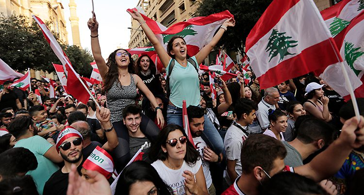 Kvinnor och män med Libanons flaggor trängs. De ser glada ut.
