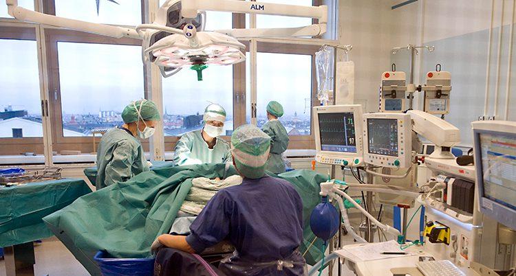 Bilden visar en operationssal på ett sjukhus. Flera personer jobbar med en patient. De som jobbar har på sig skyddskläder och skydd för munnen. Runt om finns en massa instrument och skärmar.