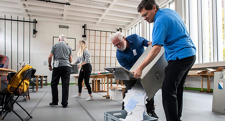 Två män tömmer en låda med röstlappar i Zürich i Schweiz. I bakgrunden syns fler valarbetare.