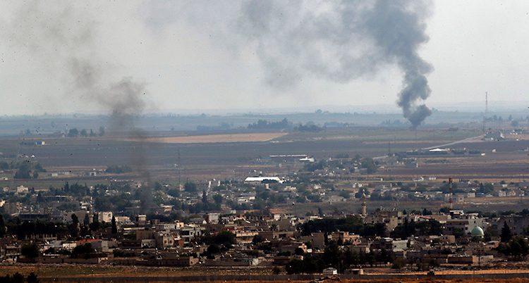 En landskapsbild på staden Ras al-Ayn. Gula och gröna fält omger en liten stad. Rök stiger mot himlen.