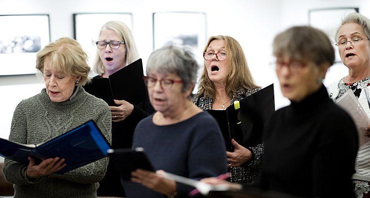 Sex äldre kvinnor håller i pärmar och sjunger tillsammans