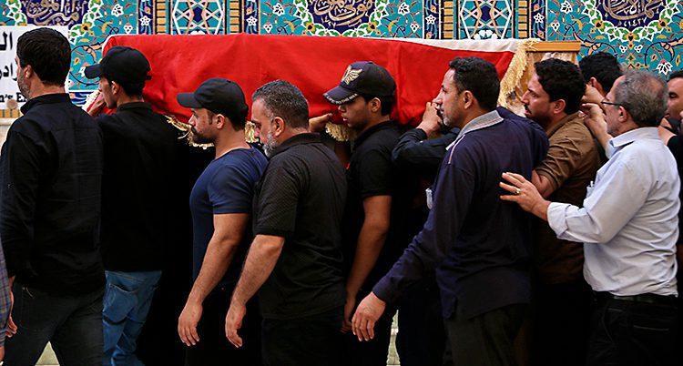 Flera män bär på en kista på en begravning.