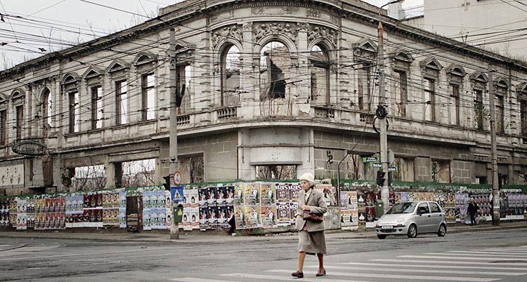 Kvinnan går framför ett trasigt hus