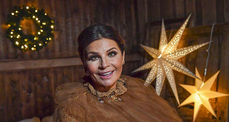 Carola Häggkvist i brunt ler mot kameran. Bakom henne en tänd adventsstjärna.