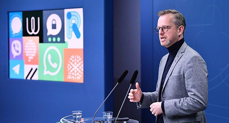 Politikern Mikael Damberg har en träff med journalister. Han står och pratar i mikrofoner. Det är en blå vägg i bakgrunden.