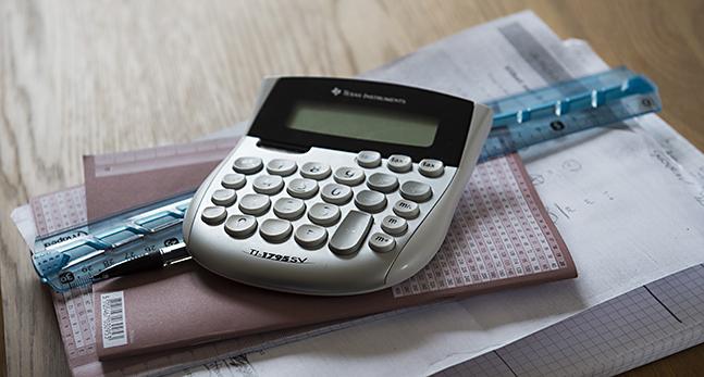 En hög med skrivböcker penna, linjal och miniräknare på ett bord.