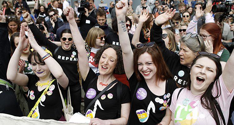 Kvinnor sträcker upp armarna och jublar.