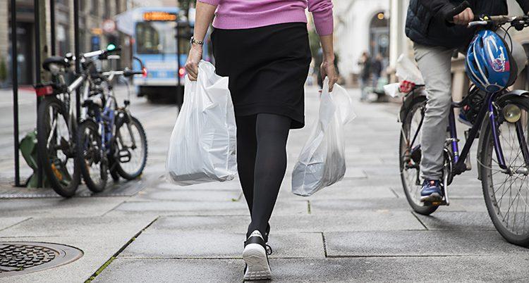 En kvinna bär två påsar i vardera hand.
