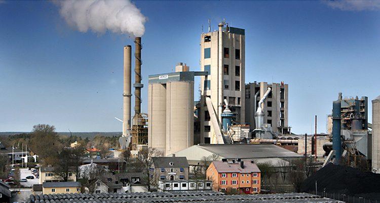 En grå fabrik med skorsten som sprutar ut rök