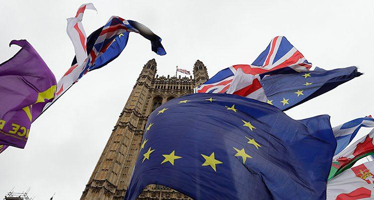 Flaggorna flyger i vinden framför en bygnad av sten