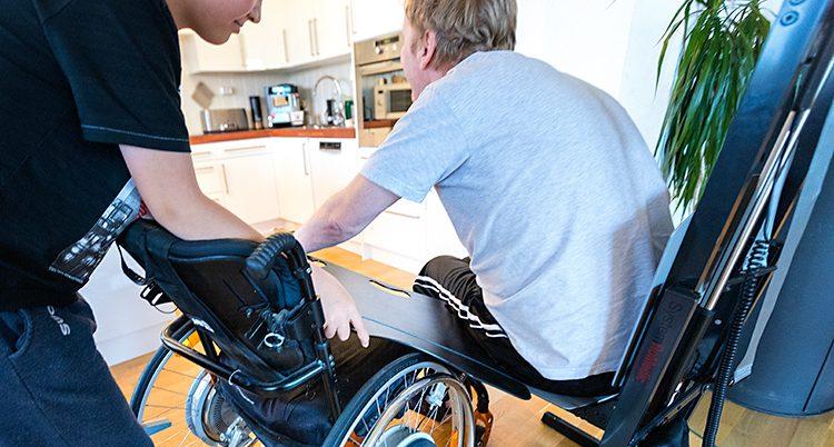 Mannen får hjälp att flytta från rullstol till en vanlig stol