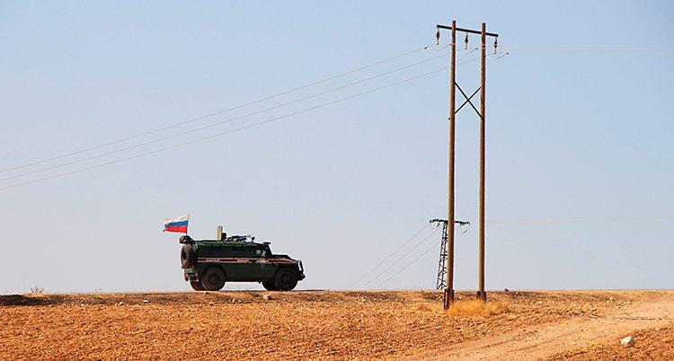 På långt håll ser man soldaternas bil köra på en väg