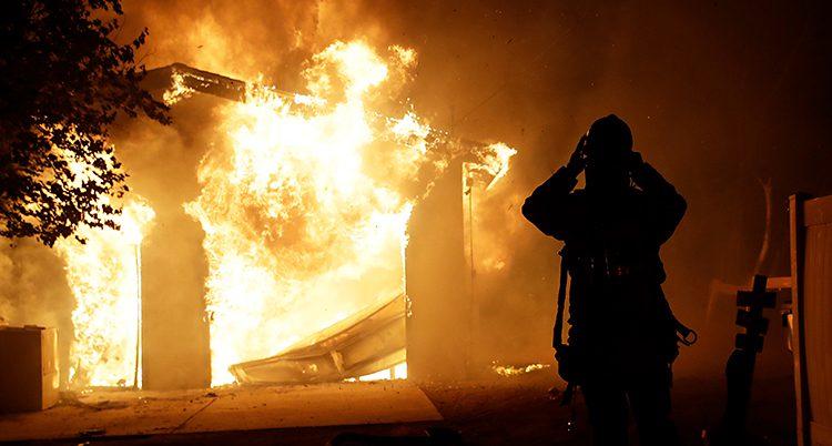 En brandman står framför en stor eld. Han försöker släcka den.