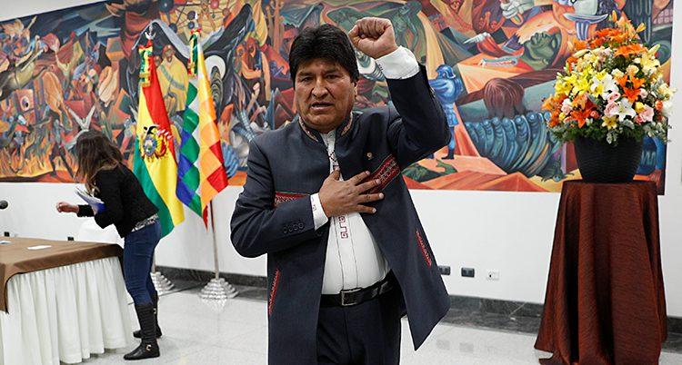 Evo Morales håller upp en arm. Han står framför en vägg målad i starka färger