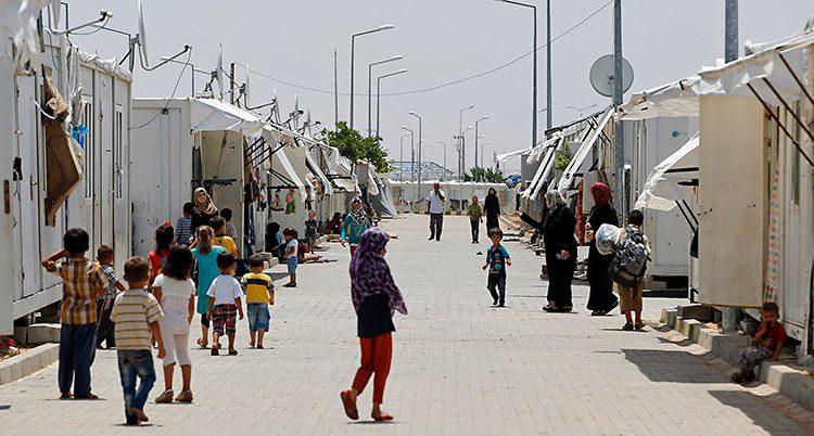 Bilden visar ett läger för flyktingar i Turkiet. Där finns flyktingar från Syrien. På en gata syns barn och kvinnor. Längs gatan finns små byggnader.