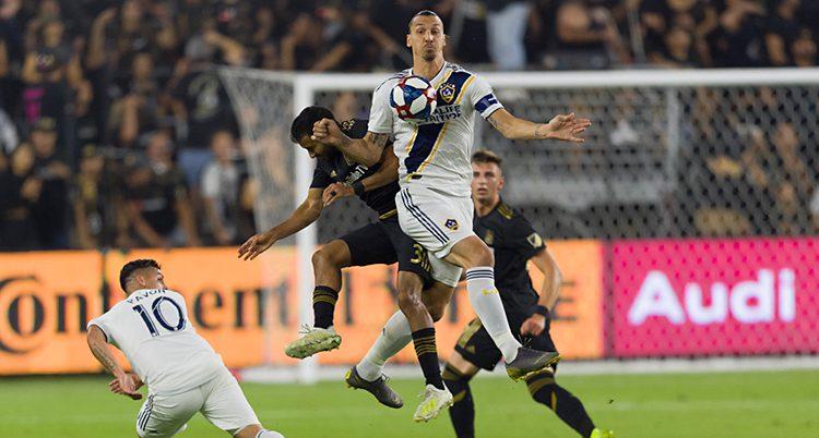 Bilden visar en match i fotboll. Zlatan Ibrahimovic hoppar upp i luften och tar bollen på bröstet. Runt om honom finns flera andra spelare.