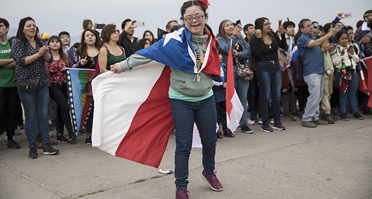 Flickan har flaggan runt halsen och en röd blomma i håret