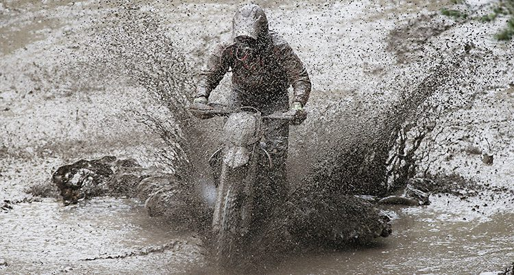 En motorcykel kör genom lera