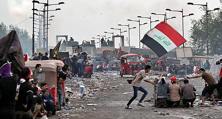 Människor på en gata. De har en flagga. Gatan är fylld av sten och bråte.