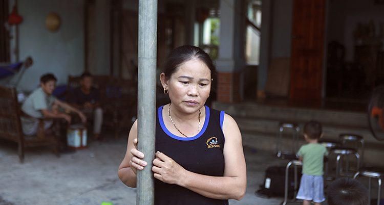 Hoang Thi Ai håller i en stolpe. Hon tittar ner i marken. Hon har ett svart linne på sig.