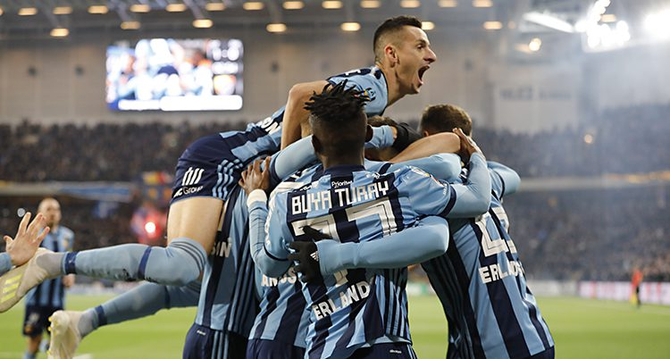 Bilden är tagen på Tele2 Arena i Stockholm. Flera spelare i Djurgården kramar varandra. De har tröjor som är randiga i mörkblått och ljusblått. I bakgrunden syns den gröna mattan och längre bort läktaren med publiken