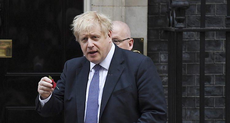 Boris Johnson har kostym och en blå slips. Han står framför en dörr.